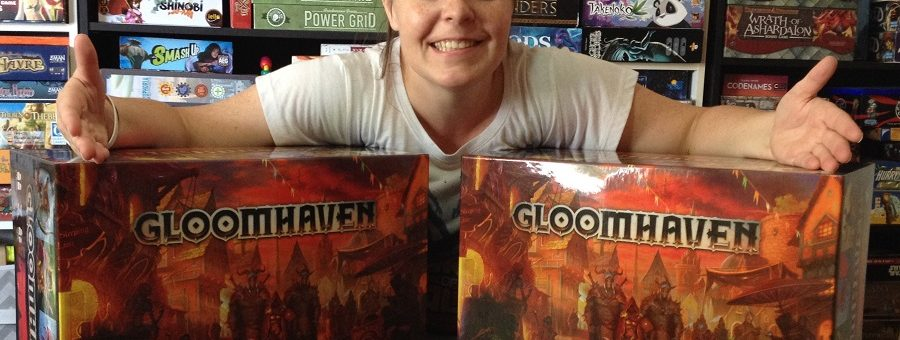 Molly showing Cephalofair Games' donations, two copies of gloomhaven